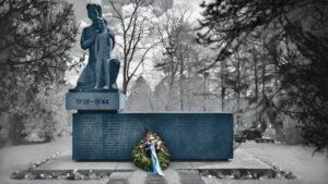 Sankarihauta naisen ja lapsen patsaalla, seppele asetettuna haudan eteen.
