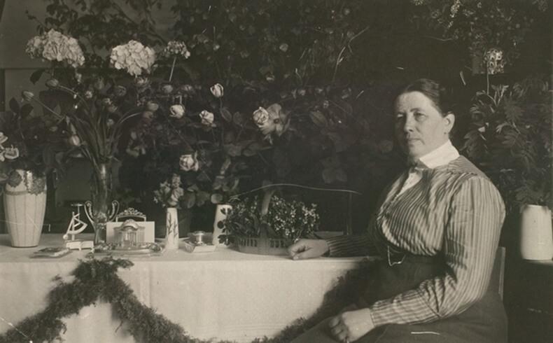 Miina Sillanpää istumassa pöydän äärellä, pöytä katettu kauniisti kukilla ja astioilla.