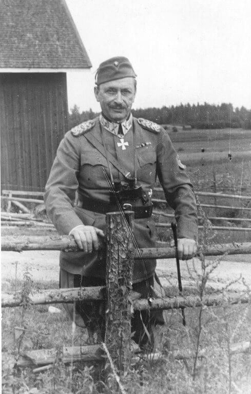 Mustavalkoisessa kuvassa sotamarsalkka Carl Gustav Emil Mannerheim aidan vierellä.