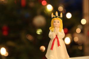Posliinikoriste-esine Lucia neidosta perinteisessä valkoisessa asussaan ja punaisessa vyössään, päässään kynttiläkruunu.